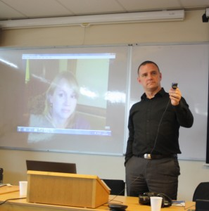 Presenter Carrie Crockett pictured on Skype (projected onto white wall) with Dan Porter standing to the right holding a microcam so she could see the audience member asking her a question