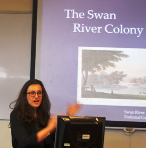 Presenter Kellie Moss talking and gesturing  in front of a powerpoint that shows a picture with title Swan River Colony