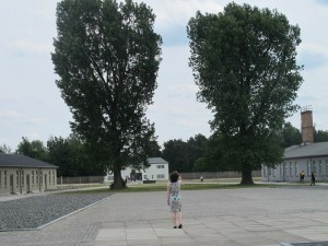 Sarah Hodgkinson walking through the courtyard at Sachenhausen towards the entrance gate