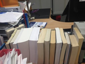 Collection of books from the back on a desk