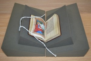 Book supports or cushions are used to protect bound volumes