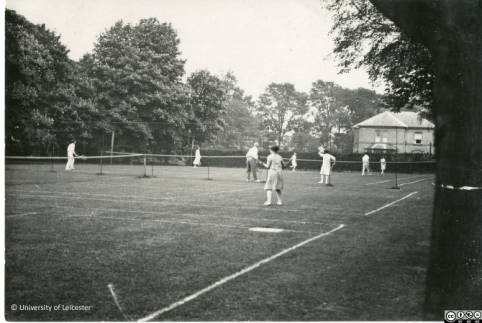 ULA/FG1/3/12: Black and white photograph of students playing tennis on the courts outside College House.