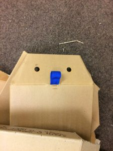 Photograph of a brown box with holes and a tag making it look like a face