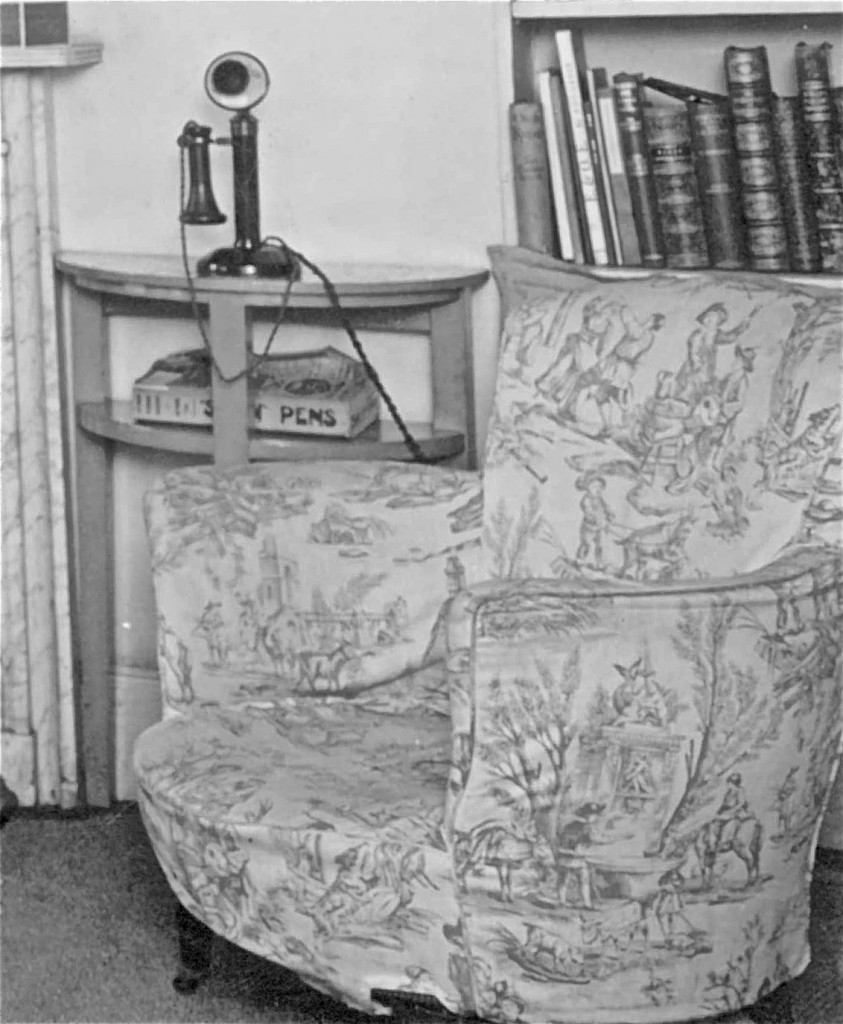 The arts and crafts chair next to the Evelyns' telephone.