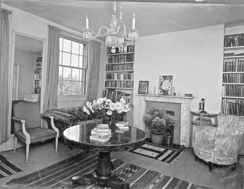 An attractive small living room from the late 1920s with central small chandelier, two armchairs, marble mantlepiece and large marble table with a vase of Michaelmas daisies on it.